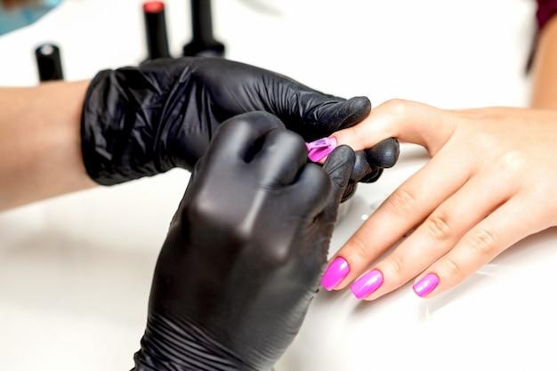 Zbliżenie mistrza manicure stosowania różowego lakieru do paznokci kobiecych w salonie paznokci