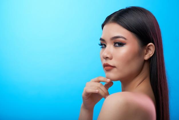 Zbliżenie młoda azjatycka kobieta z ciężkim makeup i nagimi ramionami pozuje z głową obracającą strona