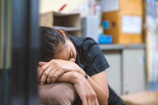 Zbliżenie młoda biznesowa dziewczyna śpi na biurku w biurze