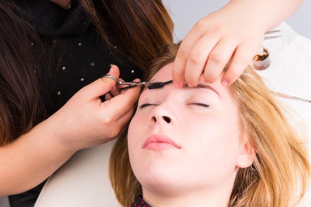 Zbliżenie: młoda blond kobieta w pozycji leżącej z zamkniętymi oczami i brwiami przyciętymi przez kosmetyczkę za pomocą nożyczek i pędzla do tuszu do rzęs w salonie spa