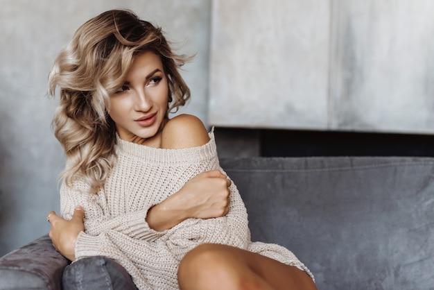Zbliżenie młoda blondynki dziewczyna siedzi na kanapie