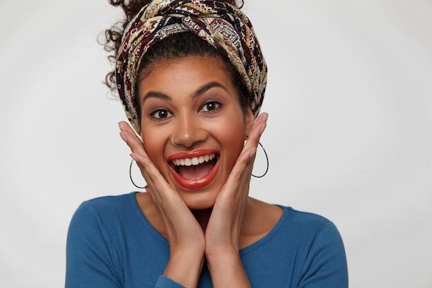 Zbliżenie: młoda brązowooka ładna ciemnowłosa dama trzyma twarz z uniesionymi rękami, patrząc szczęśliwie na aparat, odizolowane na białym tle