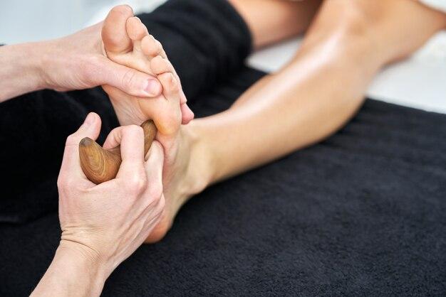 Zbliżenie: młoda kobieta korzystająca z tajskiego masażu stóp w profesjonalnym salonie