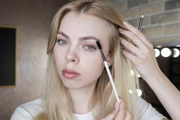 Zbliżenie: młoda kobieta noszenie makijażu przed lustrem
