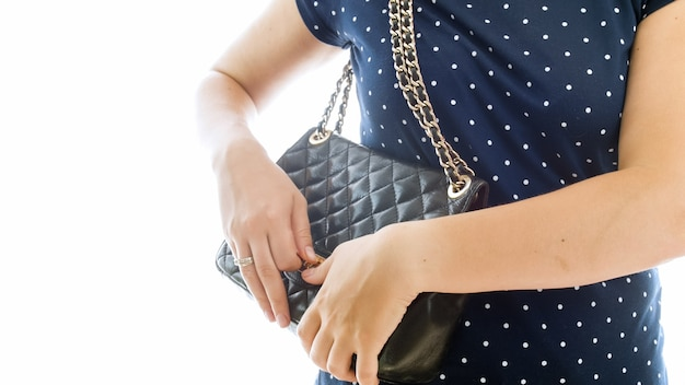 Zbliżenie młoda kobieta otwierając jej czarną skórzaną torebkę.