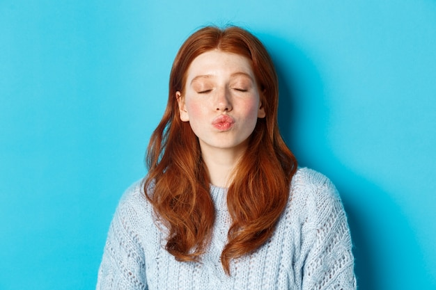 Zbliżenie: młoda kobieta z czerwonymi falującymi włosami stojąca z zamkniętymi oczami i pomarszczonymi ustami, czekająca na pocałunek na niebieskim tle.
