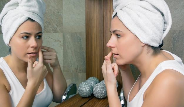 Zbliżenie młoda kobieta z ręcznikiem na włosach, ściskając trądzik pryszcz w jej pięknej twarzy przed lustrem