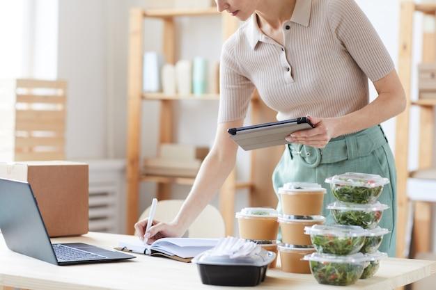 Zbliżenie: młoda kobieta za pomocą cyfrowego tabletu i robienie notatek w notesie, która pracuje w usłudze dostawy żywności