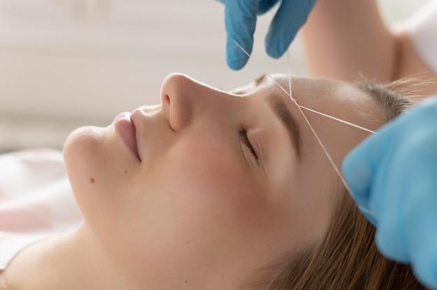 Zbliżenie: młoda kobieta zaczyna leczenie brwi