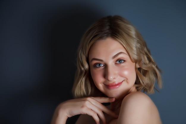 Zbliżenie młoda ładna blondynka uśmiecha się i flirtuje wygląd. kobieca emocja szczęśliwa i aktorka mistrza