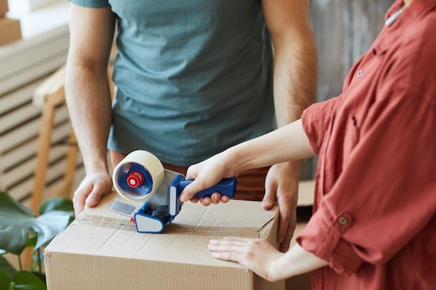 Zbliżenie: młoda para pakująca rzeczy w pudełka razem i przy użyciu taśmy klejącej podczas przeprowadzki w domu