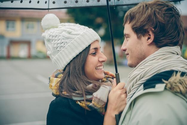Zbliżenie młoda para piękny obejmując i śmiejąc się pod parasolem w jesienny deszczowy dzień. koncepcja relacji miłości i para.