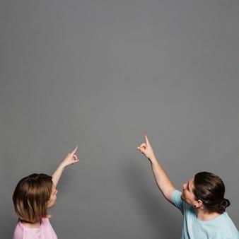 Zbliżenie: młoda para, wskazując palcami w górę przeciwko szarej ścianie
