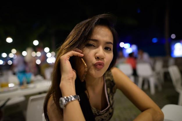 Zbliżenie młoda piękna kobieta azji rozmawia przez telefon komórkowy