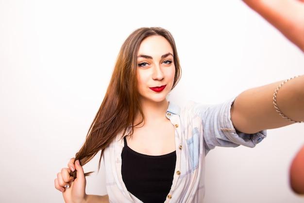 Zbliżenie: młoda piękna kobieta przy selfie. na białym tle biały