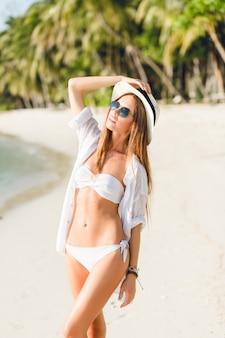 Zbliżenie: młoda seksowna szczupła dziewczyna stojąca na plaży na sobie białe bikini. nosi białą koszulę, ciemne okulary przeciwsłoneczne i słomkowy kapelusz. jest opalona i stylowa.