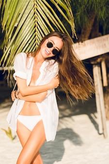 Zbliżenie: młoda seksowna szczupła dziewczyna stojąca na plaży na sobie białe bikini z zielonym liściem palmowym. nosi białą koszulę i ciemne okulary przeciwsłoneczne. ona się bawi