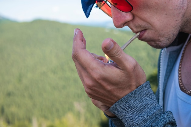 Zbliżenie młodego człowieka palącego marihuanę na zewnątrz konopie tępe w męskiej dłoni