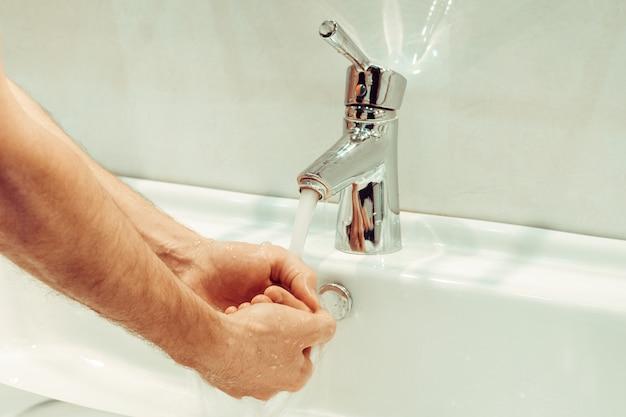 Zbliżenie młodego człowieka rasy kaukaskiej mycie rąk mydłem w zlewie łazienki higieny osobistej