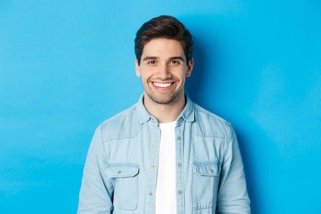 Zbliżenie młodego człowieka sukcesu uśmiechającego się do kamery, stojącego w swobodnym stroju na niebieskim tle
