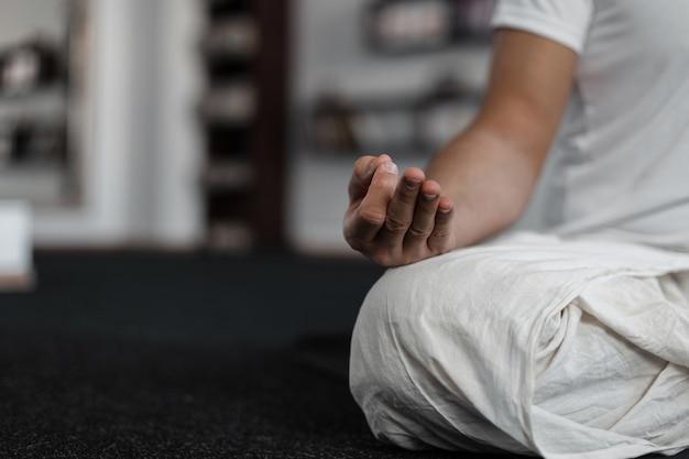 Zbliżenie młodego człowieka w medytacji na siłowni. koncepcja jogi i zdrowego stylu życia. czas relaksu.