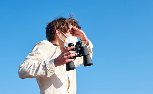 Zbliżenie młodego człowieka z lornetką w masce blokującej słońce ręką patrząc w dal