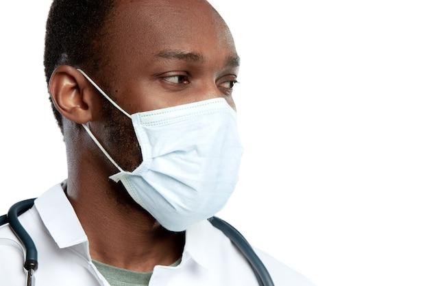 Zbliżenie młodego lekarza ze stetoskopem i maską na białym tle na białej ścianie
