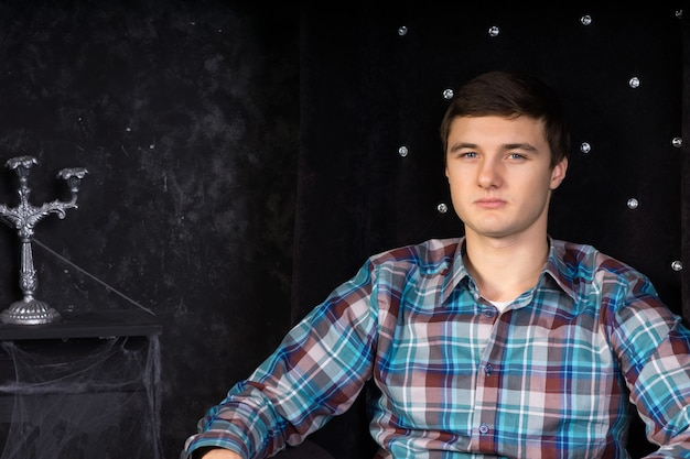 Zbliżenie młodego mężczyzny siedzącego w pluszowym czarnym krześle z wysokim oparciem w otoczeniu nawiedzonego domu