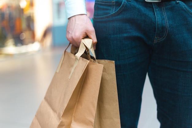 Zbliżenie młodego mężczyzny stylowe spaceru w centrum handlowym z torby na zakupy przyjazne ekologii w parze z towarami i ubraniami. sprzedaż, rabat wyprzedany koncepcja. sezonowa wyprzedaż.