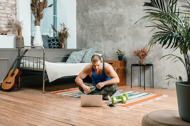 Zbliżenie młodego mężczyzny w stroju sportowym odpoczywa, siedzi na podłodze w domu, ogląda film i uczy się z laptopa, sieci społecznościowej