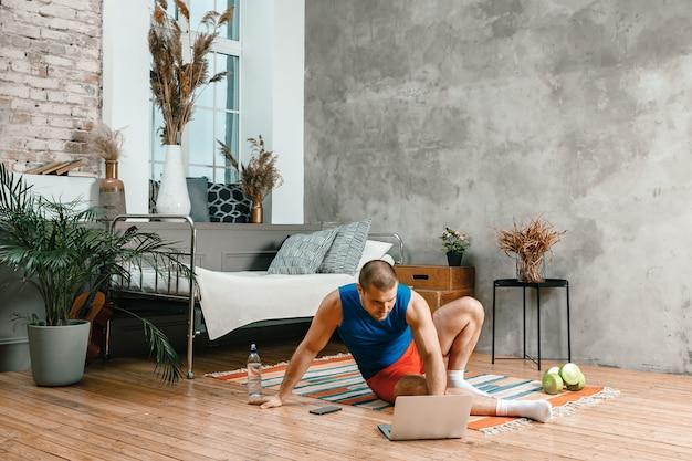 Zbliżenie młodego mężczyzny w stroju sportowym odpoczywa, wyciąga się na podłodze w domu, ogląda film i uczy się z laptopa, sieci społecznościowej