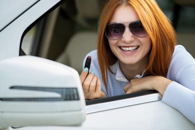 Zbliżenie młodego rudowłosego kierowcy poprawiającego makijaż z ciemnoczerwoną pomadką patrzeje w samochodowym lusterku wstecznym za kierownicą pojazdu.