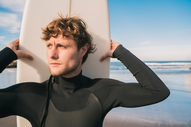 Zbliżenie młodego surfera stojącego na plaży ze swoją deską surfingową i ubranym w czarny strój surfingowy
