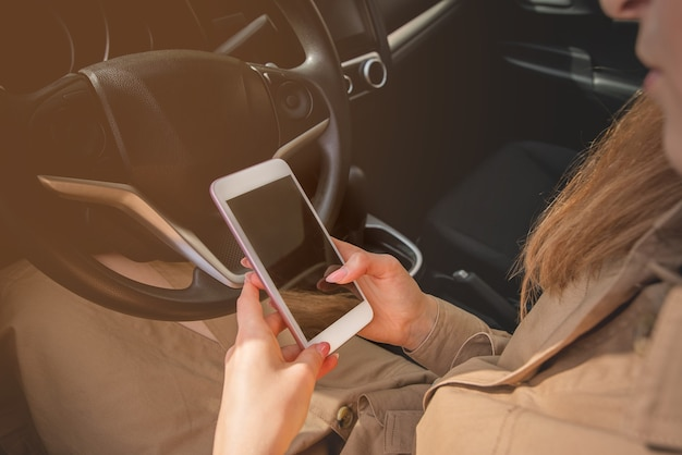 Zbliżenie młodej bizneswoman sprawdzania swojego smartfona siedząc na siedzeniu kierowcy swojego samochodu