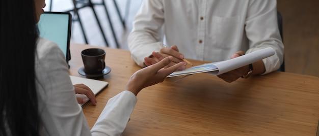 Zbliżenie młodej bizneswoman, wyjaśniając jej biznesplan współpracownikowi