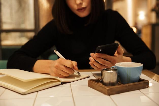 Zbliżenie młodej brunetki siedzącej przy stoliku kawiarnianym w pomieszczeniu, piszącej na notebooku, trzymającej telefon komórkowy