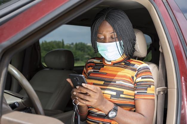 Zbliżenie młodej czarnej kobiety za pomocą swojego telefonu siedząc w samochodzie, ubrana w maskę