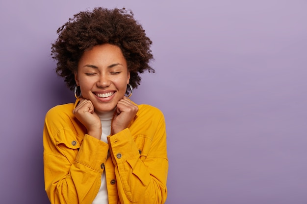 Zbliżenie młodej damy z fryzurą afro uśmiecha się radośnie, wyobraża sobie coś przyjemnego, nosi modną żółtą koszulę, odizolowaną na fioletowej ścianie