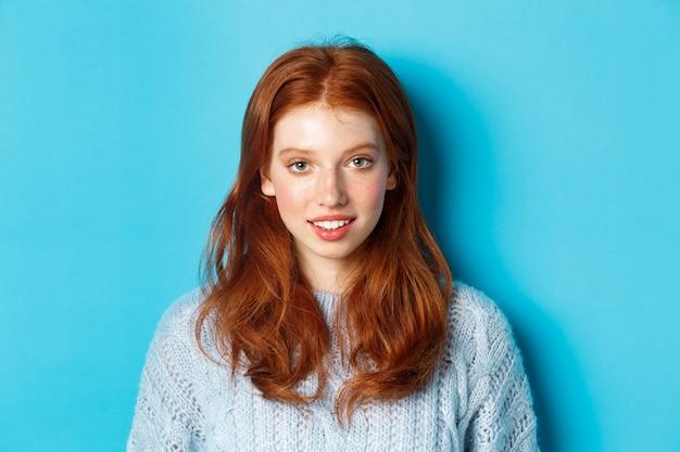 Zbliżenie młodej dziewczyny cute rude uśmiecha się do kamery, stojąc na niebieskim tle.