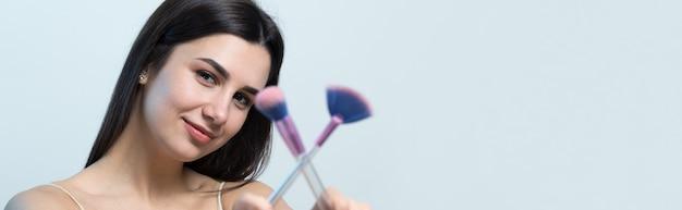 Zbliżenie młodej dziewczyny w jasnym topie na białym tle robi makijaż twarzy