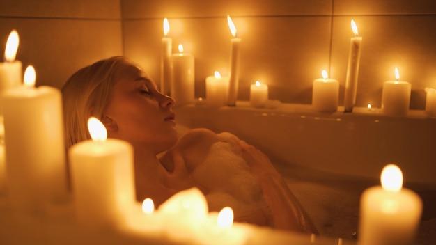 Zbliżenie młodej kobiety biorącej kąpiel w otoczeniu świec