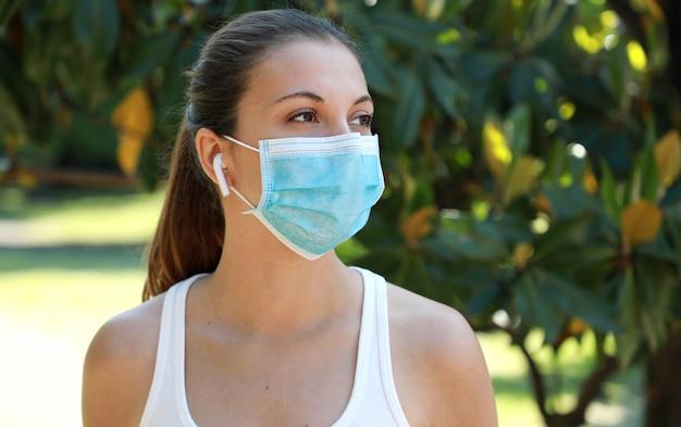Zbliżenie młodej kobiety fitness z maską chirurgiczną i bezprzewodowymi słuchawkami w parku miejskim
