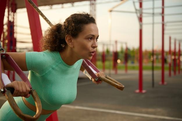 Zbliżenie młodej kobiety lekkoatletycznego z idealnym ciałem w odzieży sportowej robi pompki z paskami zawieszenia fitness w boisku. atrakcyjna kobieta afroamerykanów, pracująca na zewnątrz o wschodzie słońca.