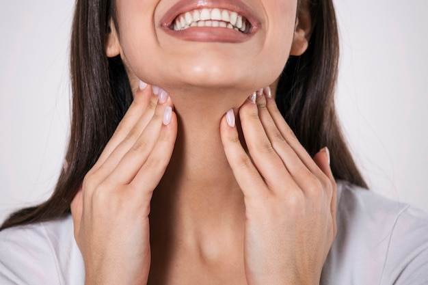 Zbliżenie młodej kobiety ocierającej się o stan zapalny migdałków, problem z zapaleniem migdałków, przycięte.