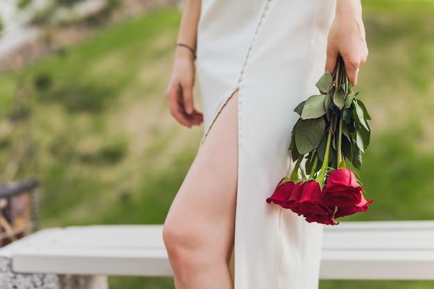 Zbliżenie młodej kobiety ręki trzymającej czerwone kwiaty róży na tle zewnątrz.