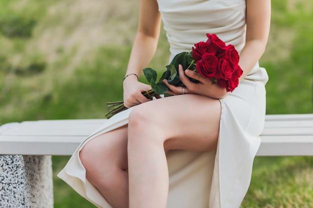Zbliżenie Młodej Kobiety Ręki Trzymającej Czerwone Kwiaty Róży Na Tle Zewnątrz. Premium Zdjęcia