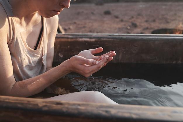 Zbliżenie młodej kobiety siedzącej w wannie na zewnątrz i myjącej twarz