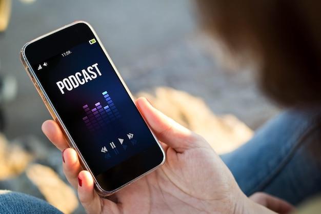 Zbliżenie młodej kobiety słuchania podcastu na swoim telefonie komórkowym