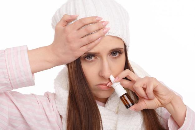 Zbliżenie młodej kobiety trzymając aerozol do nosa