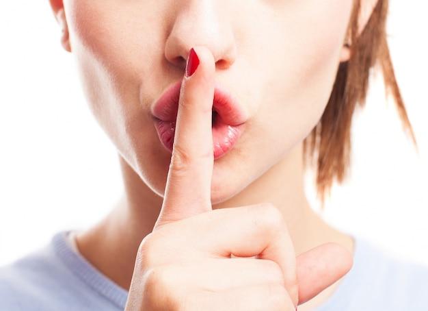 Zbliżenie młodej kobiety, trzymając palec na ustach